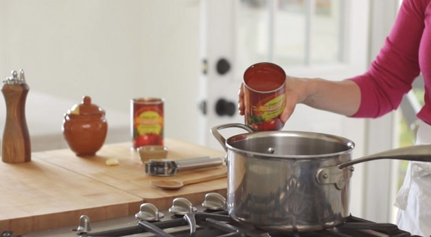 Adding red sauce to large pot