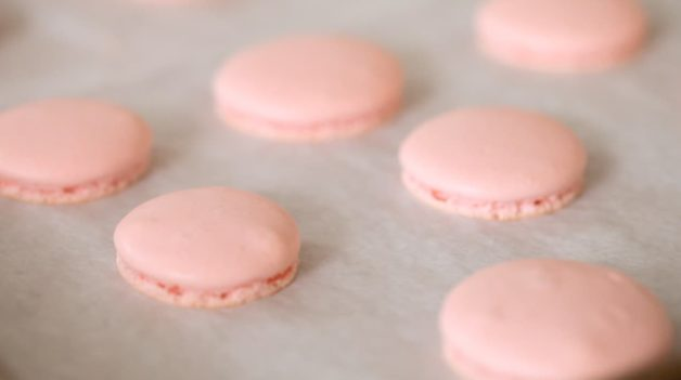 Macaron Shells with feet on a baking sheet