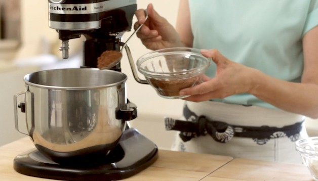 Cocoa powder being spooned into a stand mixer