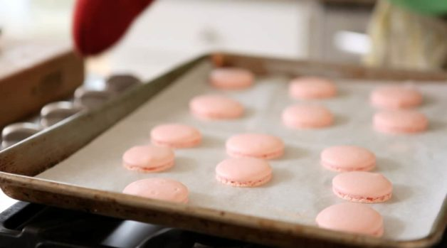 Pink Macaron shell coming out of the oven on a baking tray
