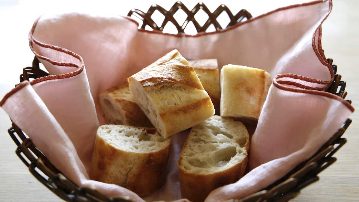 Sliced Baguette Bread in a bread basket with Pink cloth