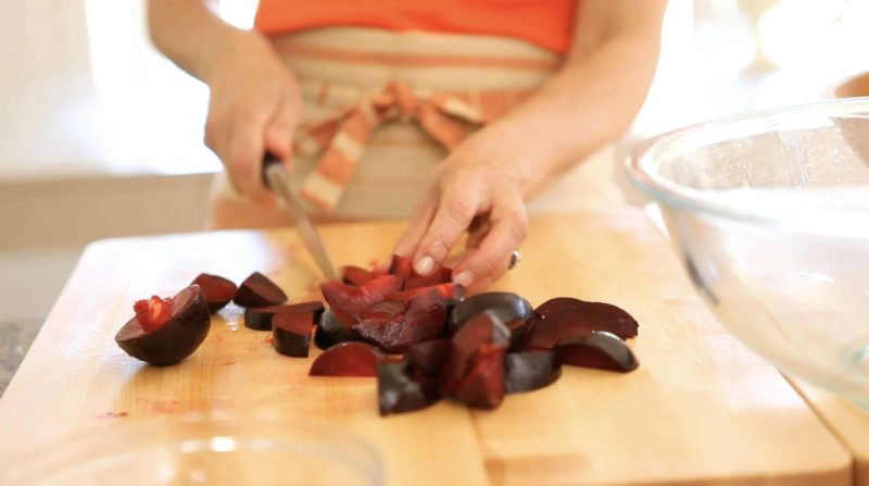 Easy Plum Crumble Recipe plums being chopped on a wood cutting board