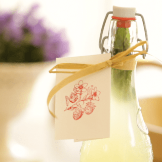 Homemade Lemonade served in a glass container with purple flowers in the background