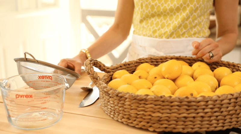 homemade lemonade ingredients and tools on a wood surface