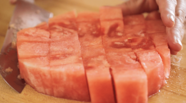 How to Make Watermelon Lemonade the watermelon sliced into chunks on a wood surface