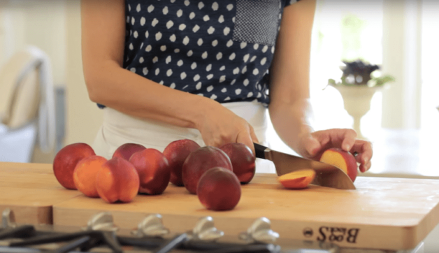 peaches being sliced on a wood board for summer fruits crumble recipe