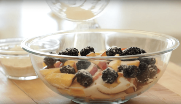fruit being mixed with sugar and flour in a large clear bowl for a summer fruits crumble recipe