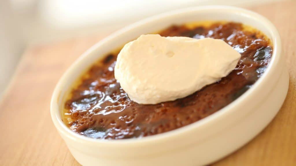 Best Crème brûlée Recipe served in a white ramekin with a dollop of cream on top