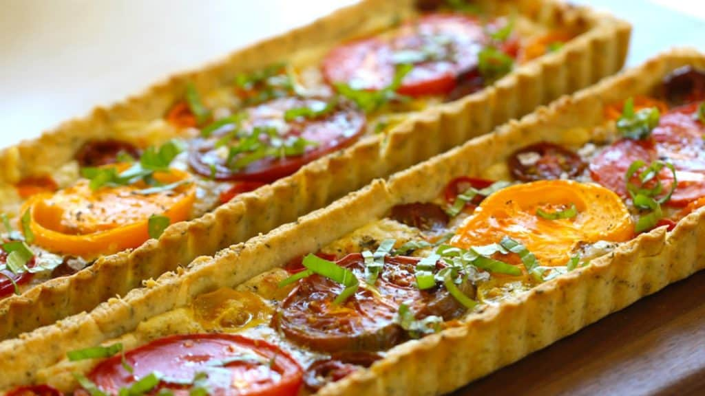 tomato tart provencal baked and served on a wood surface