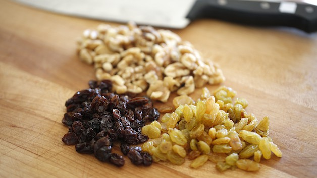 a cutting board with a grouping of raisins, yellow raisins and chopped walnuts