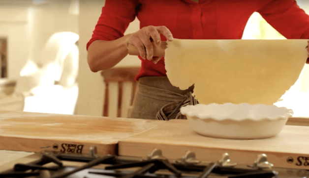 pie dough being rolled into pie dish with a rolling pin for a recipe on how to make a cherry pie