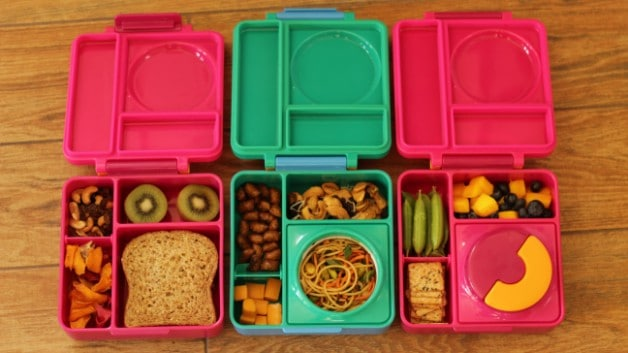 three Pink and green omie lunchboxes open and filled with food