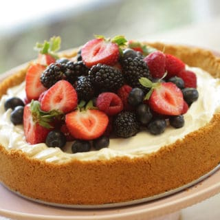 Triple Berry, No-Bake Cheesecake Recipe served on a light pink cake stand