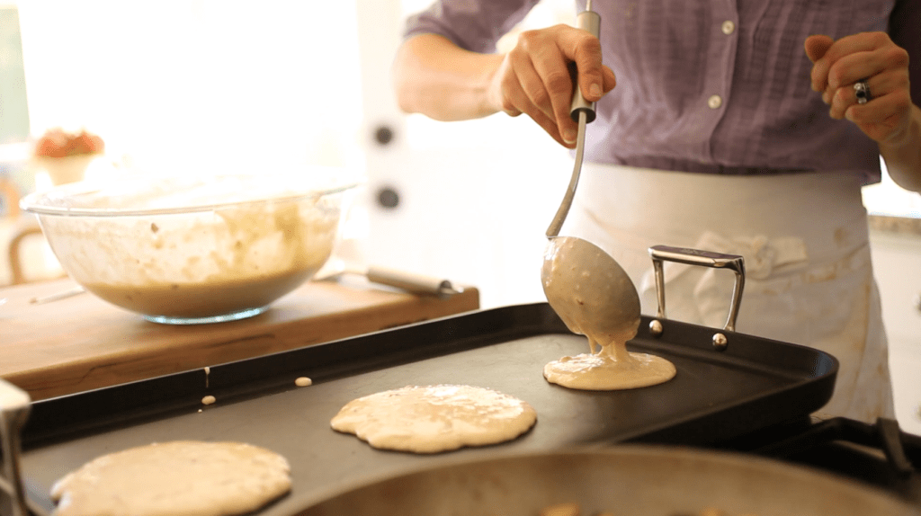 the best apple cider pancakes batter being spooned on to a hot griddle to cook
