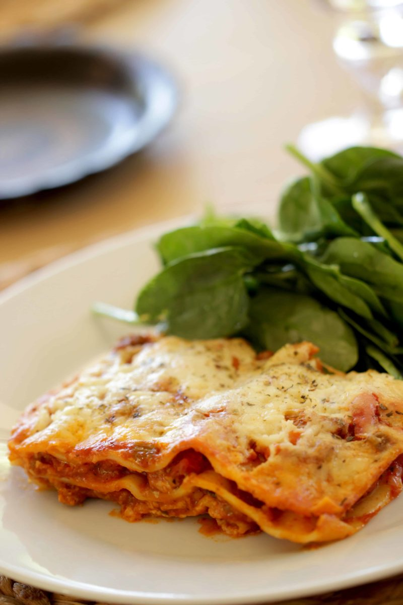 How to Make Lasagna recipe served with salad on a white plate
