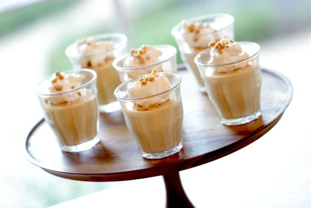 Salted Caramel Puddings served with fresh whipped cream in little glass jars on a wood surface