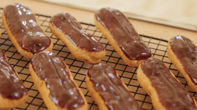 Chocolate Eclair Recipe made and decorated and cooling on a black wire rack