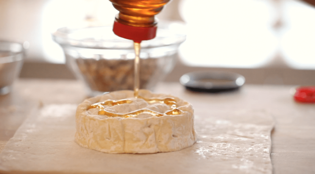 honey drizzled on top of a brie wheel for a baked brie in puff pastry recipe