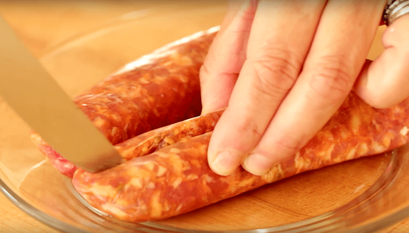 italian sausage being cut out of casing for a How to Make Lasagna recipe