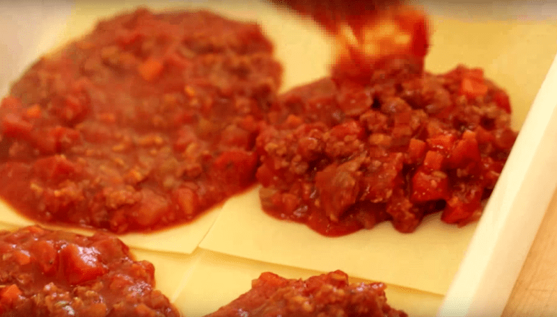 meat sauce being added to lasagna for a How to Make Lasagna recipe