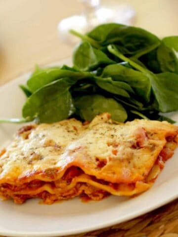 Lasagna recipe served with salad on a white plate