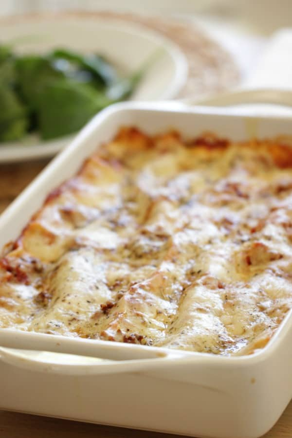 Lasagna in a large white baking casserole on table
