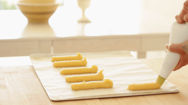 Lines of choux pastry piped out on a parchment-lined baking sheet