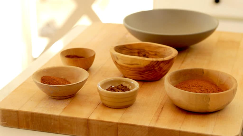 A selection of spices in small bowls on a cutting board for homemade pumpkin pie spice