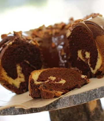 Chocolate Marble Cake Recipe on a wooden cake stand sliced open to see swirls