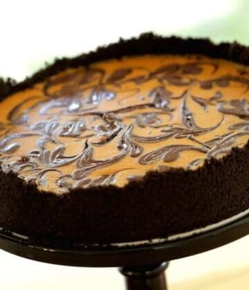 Pumpkin Cheesecake with Chocolate Swirl served on a cake stand on a wood surface