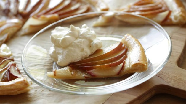 A slice of an Easy Pear Tart on a glass plate with whipped cream