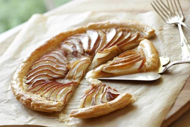 Pear Tart with Puff Pastry on cutting board with parchment paper and forks
