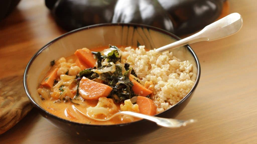 Vegetarian Thai Red Curry Recipe in a shallow bowl with rice and cutlery