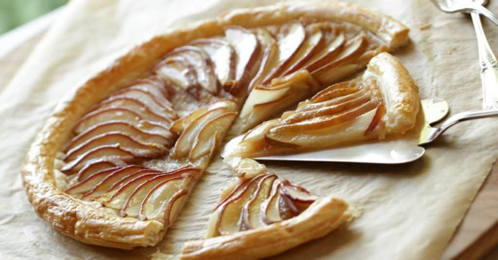 Pear tart with puff pastry sliced on parchment paper
