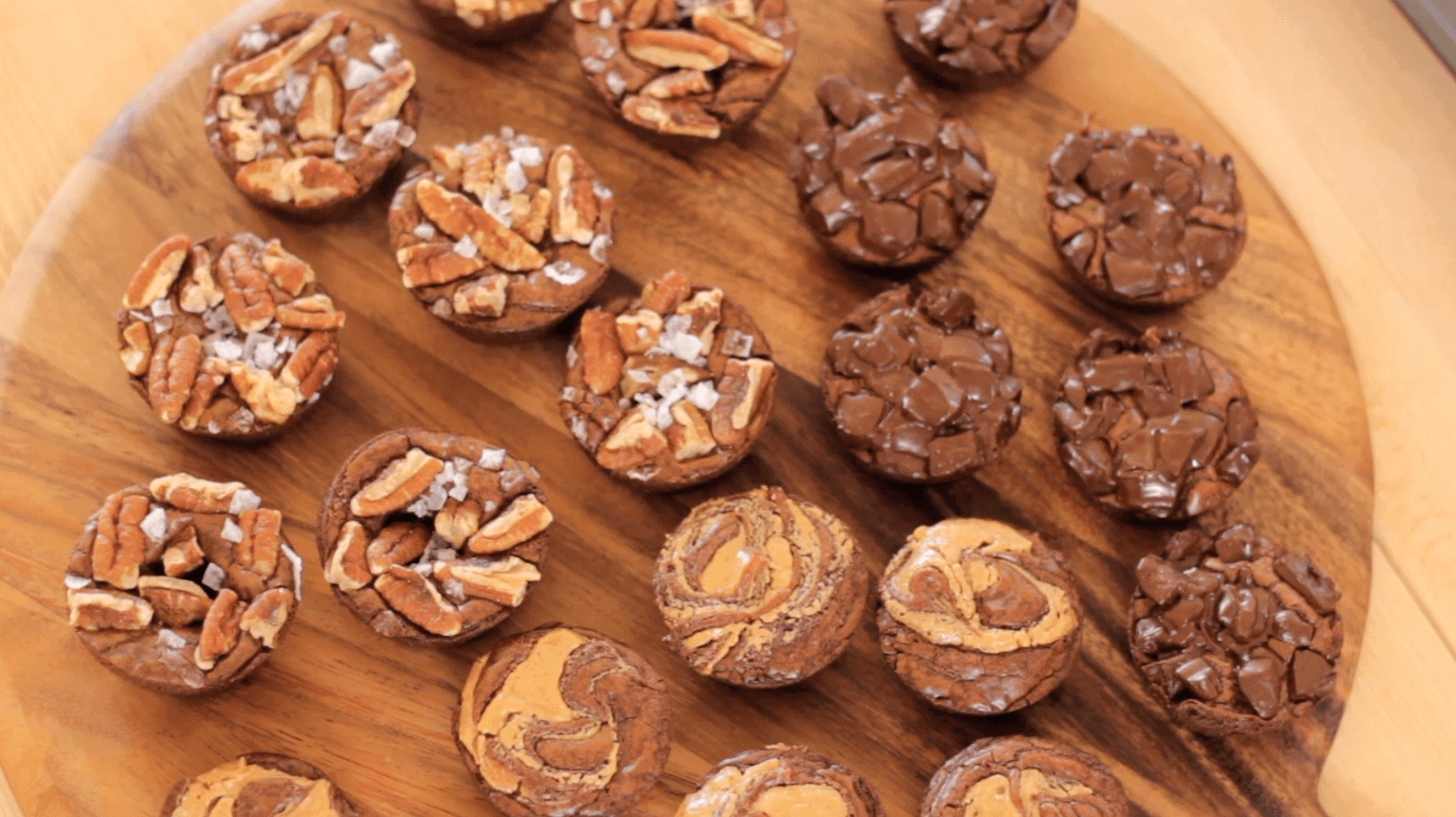 Brownie Bites on a wooden board with different toppings