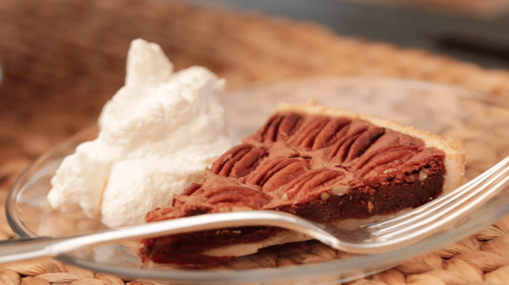 Chocolate Pecan Tart sliced and put on a clear plate with a dollop of whipped cream and a fork