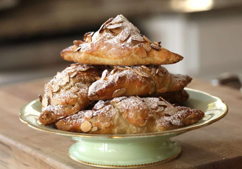 Almond Croissants piled high on a green cake stand