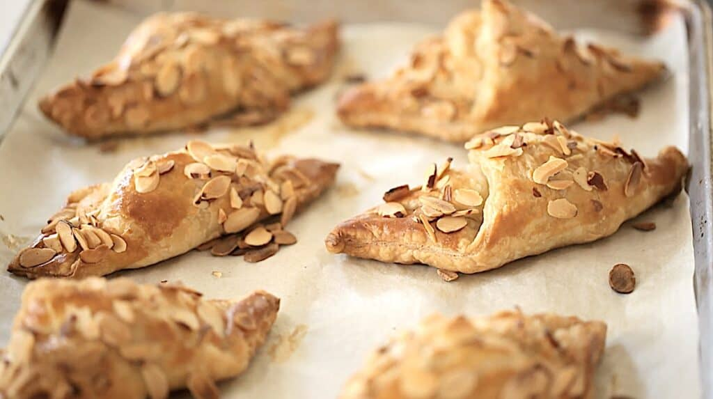 freshly baked almond croissants on a sheet pan