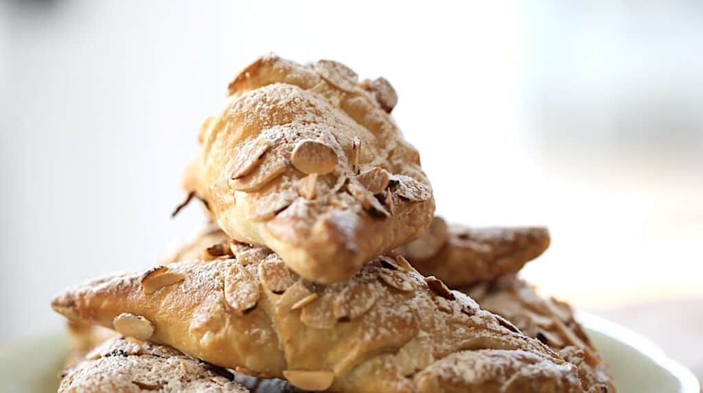 close up of croissants dusted with powdered sugar