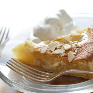 Pear Almond Tart Recipe served with some whipped cream on a white plate with a silver fork