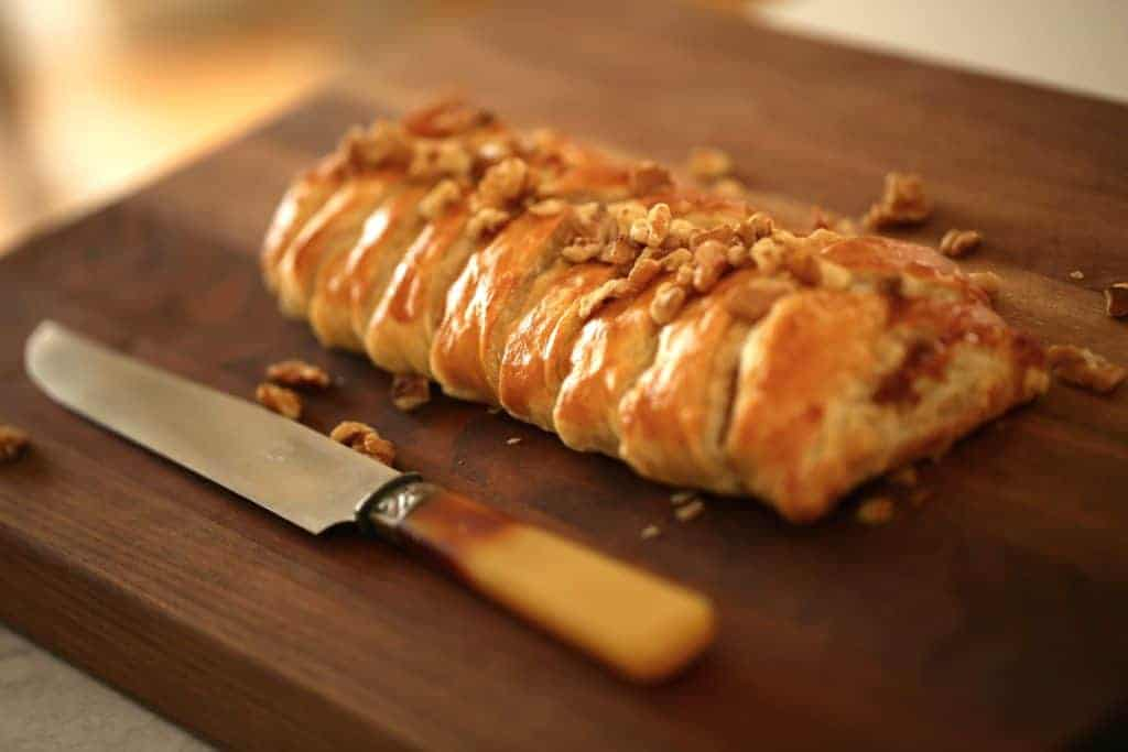 Fig and Brie Braid in Puff Pastry on a Walnut Board with a Knife