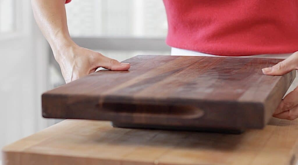 a person placing a cutting board onto of pan to flip it over and release shortbread
