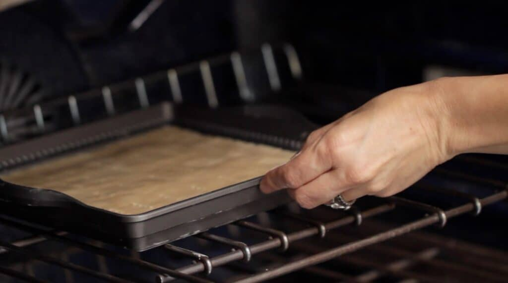 placing shortbread pan in the oven to bake