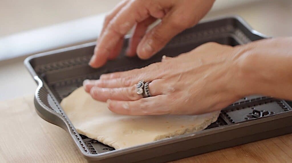 a person pressing dough into a shortbread pan