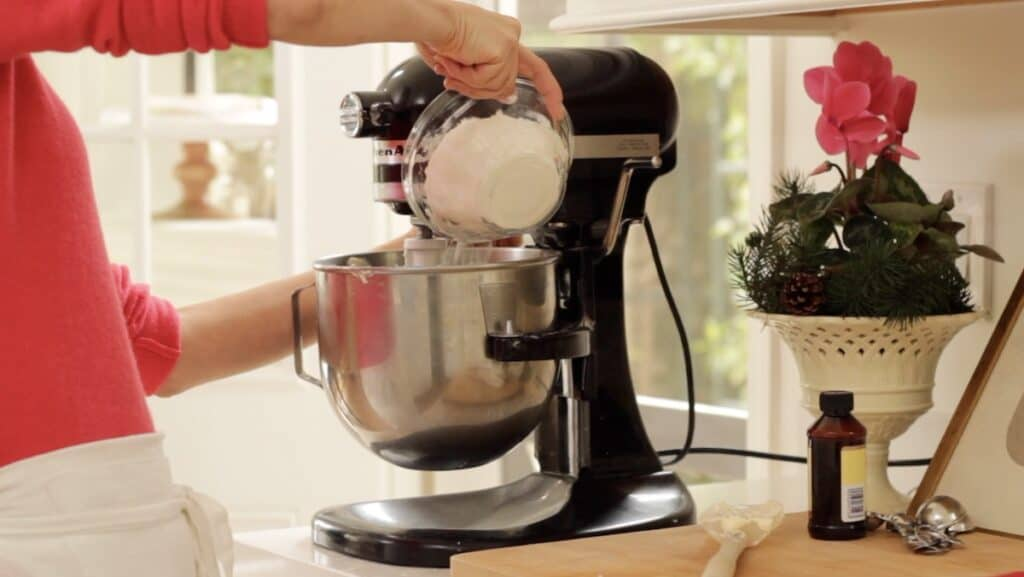 adding dry ingredients to a stand mixer