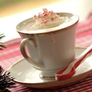 Peppermint Hot Chocolate recipe served in a white tea cup and saucer with a candy cane spoon on the side served on a red tablecloth