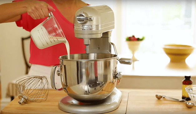 heavy cream being poured into a silver kitchen aid stand mixer for a no-bake pumpkin cheesecake mousse recipe