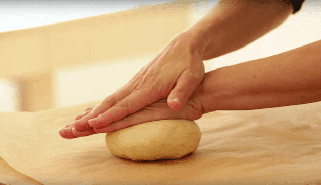 tart dough being rolled on a wood board