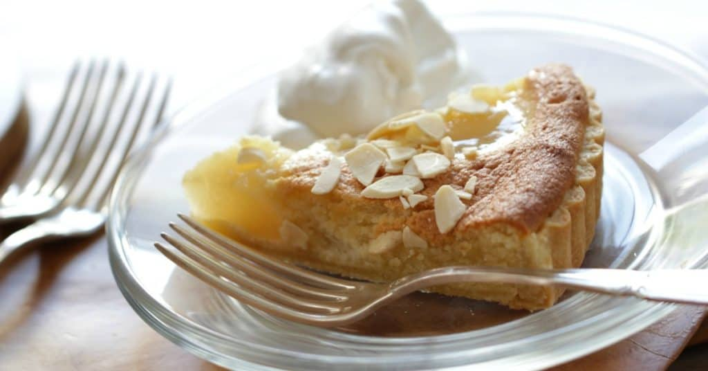 a slice of Pear Almond Tart on a plate with a dollop of whipped cream and a fork