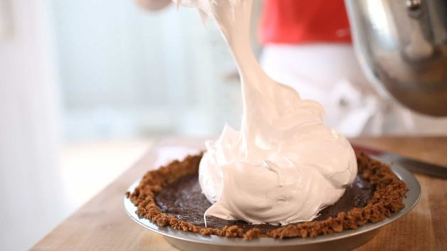 placing marshmallow on top of a S'More Pie Recipe